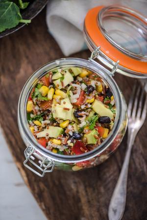 rustic food: super food salad with quinoa and avocado on rustic jar