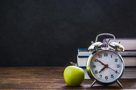 retro alarm clock and classroom chalkboard, back to school concept