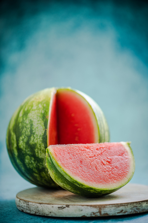 cut off: whole watermelon with cut off slice on wooden board Stock Photo