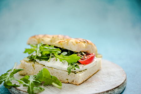 rucola: sandwich with rucola, served on wooden board