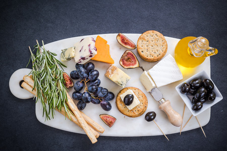 cheese selection on marble board with red wine,grapes,olives herbs and honey Stock Photo