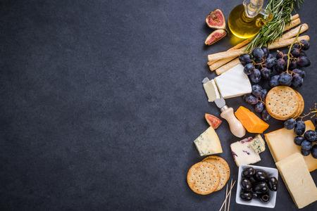 cheese selection border background on dark slate Standard-Bild