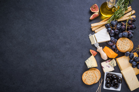 cheese selection border background on dark slate Archivio Fotografico