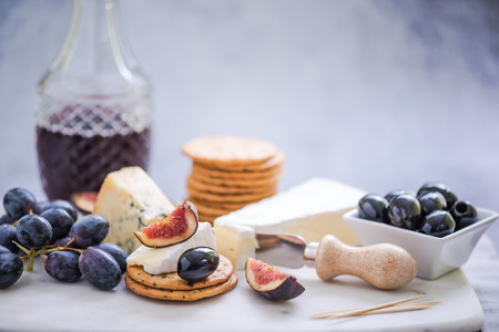 crackers with selection of cheese,grapes,olives and fig Stock Photo