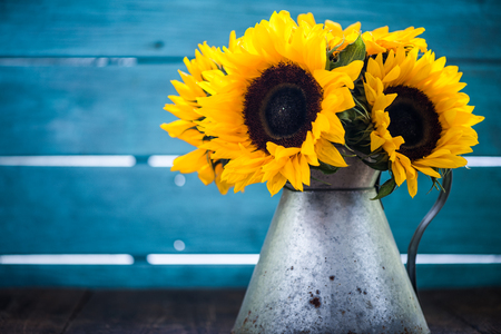 sunflowers bouquet in vintage vase on wooden table Stock Photo