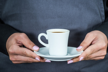 hospitality staff: waitress holding cup of espresso coffee