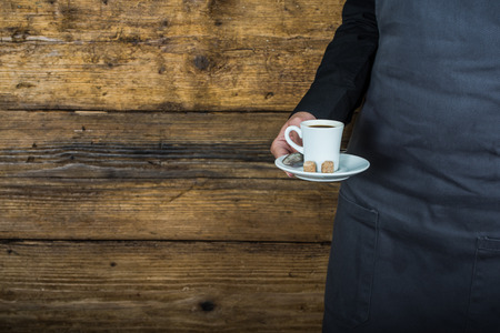 hospitality staff: waitress hold coffee in hand wearing apron