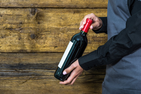 hospitality staff: waitress show wine bottle, wooden background copy space