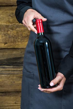 hospitality staff: waitress oppening red wine bottle, gray apron