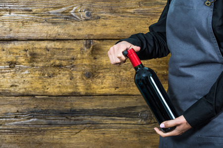 hospitality staff: waitress offering red wine, copy space Stock Photo
