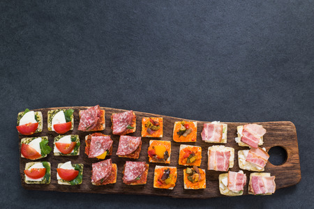 antipasti: traditional antipasti snack on wooden board, from above view Stock Photo