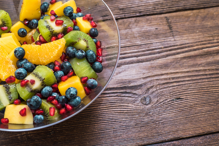fruity salad: healthy detox dieting fruity salad in glass bowl on wooden table