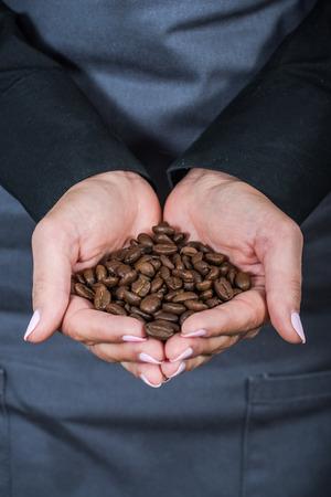 hospitality staff: barttender holds coffee beans handfull Stock Photo