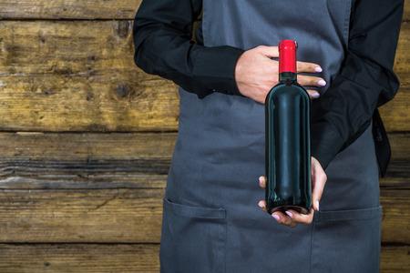 hospitality staff: waitress offering wine choice, holding red wine bottle