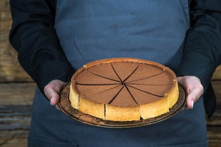 hospitality staff: waitress holding chocolate tort perfectly sliced Stock Photo