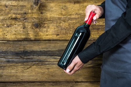 hospitality staff: waitress showing red wine bottle to restaurants clients