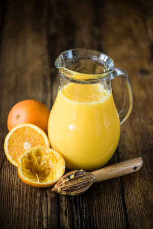 pincher: fresh orange juice in pincher, in wooden background and low moody light Stock Photo