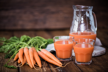 pincher: carrot juice in pincher on wooden table