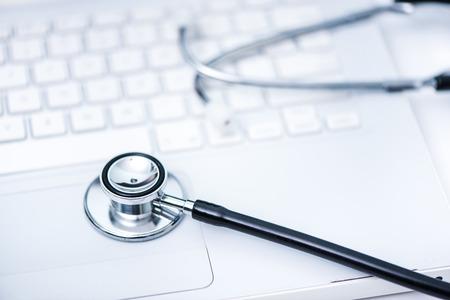 stetoscope: stetoscope on desktop computer keyboard, on line doctor concept