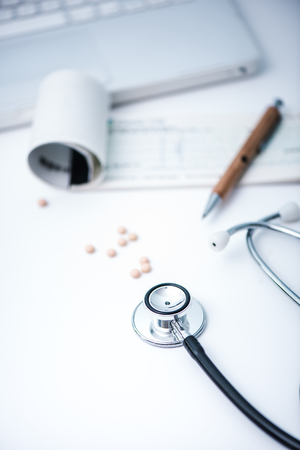 stetoscope: writing medical prescription on desk