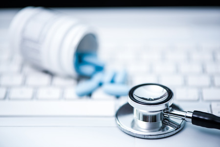 stetoscope and blue pills on keyboard, internet doctor consultations concept