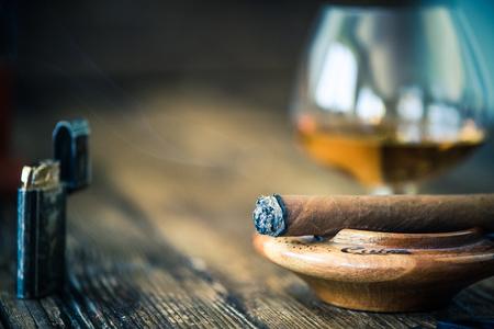 smoking cigar close up view, in wooden ashtray