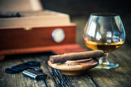 glass of cognac and cigar in ash tray Stock Photo