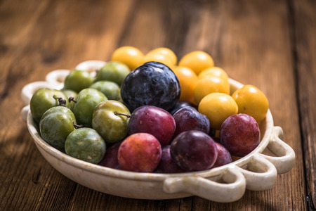 to and fro: varieties of plums in rustic bowl fro orchand, autumn seasonal fruit