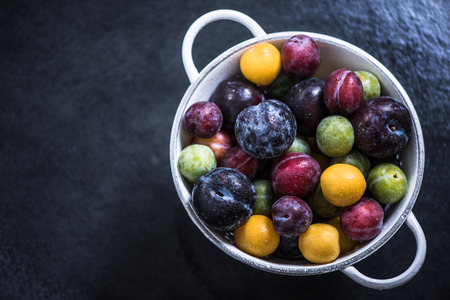 ripe colorful plums from orchand in rustic colander