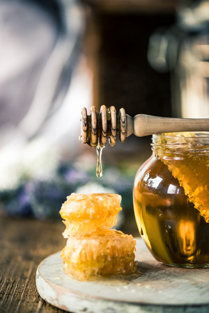 Honey dripping over vax comb on wooden table