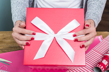 woman hands hold big red Christmas gift box with white ribbon Stock Photo