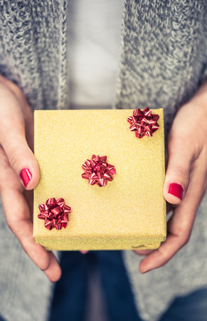 jewlery: woman hands hold small golden jewlery gift box for Christmas or New Year Stock Photo