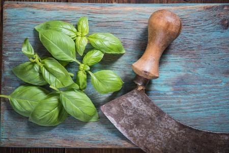 leaf cutter: Vintage kitchen herb knife and fresh basil on wooden board