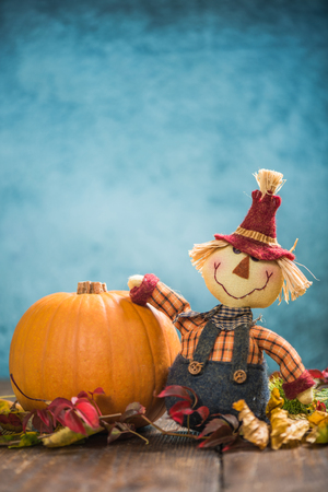 colorful frame: Funny scarecrow holding pumpkin in autumnal background Stock Photo