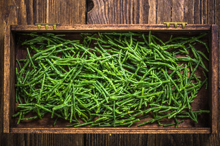 Samphire seafood weed in wooden crate, overhead view Archivio Fotografico