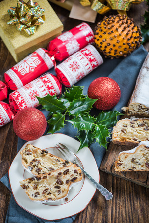 Festive Christmas cake, stollen with raisins served on table with Xmas festive ornaments