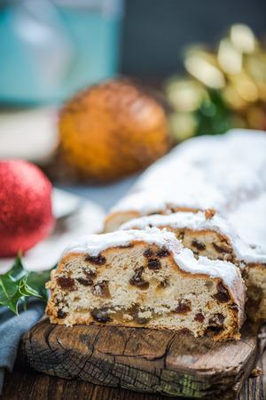 Traditionelle Weihnachten Stollen Kuchen in Scheiben geschnitten, Holztisch mit festlichen docoration