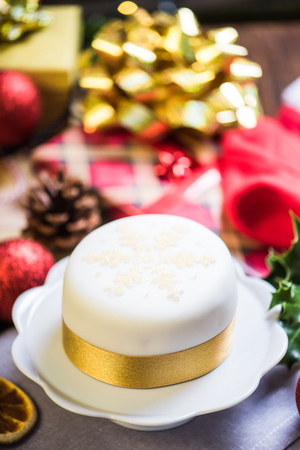 Traditional Christmas cake with festive decorations on table Stock Photo
