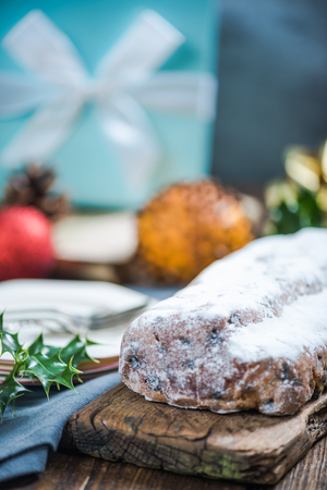Christmas stollen cake on festive decorated table with Xmas ornaments Stock Photo