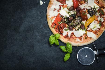 woodfired: wood-fired traditional Italian pizza, overhead view on dark slate