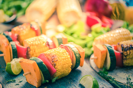 grilled vegetable skewers with fresh herbs on wooden board, high angle shot
