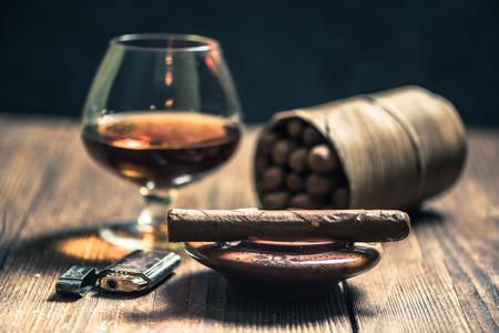 쿠바 시가와 나무 책상에 알코올의 유리