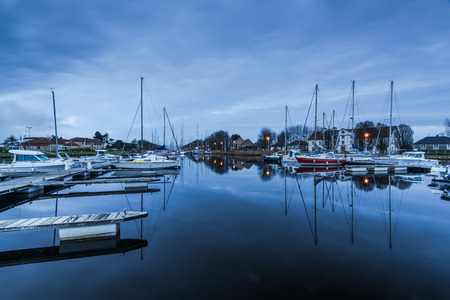 manche: Harbour quay in historic city of Carentan,France at twilight , long exposure reflections in water.