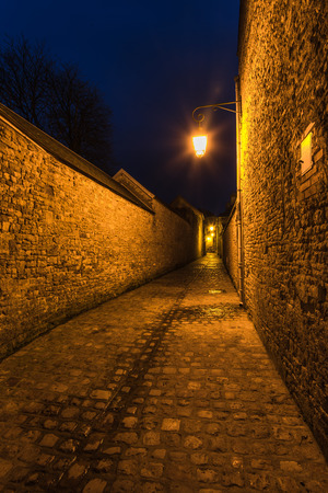archways: Old french mediewal cobbled street in historic city of Carentan,France at dusk Stock Photo