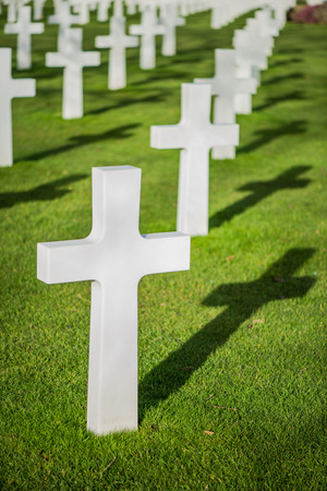 White crosses on graveyard with shadow on grass