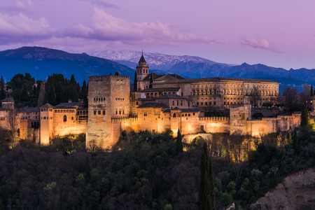 Illuminated Arabic Alhambra palace in Granada,Spain with Sierra Nevada snowy mountains in background Editorial