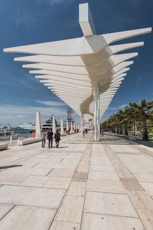 Malaga, Spain - April 20, 2017:  Waterfront in Malaga, Spain with tourist walking relaxed in sun.