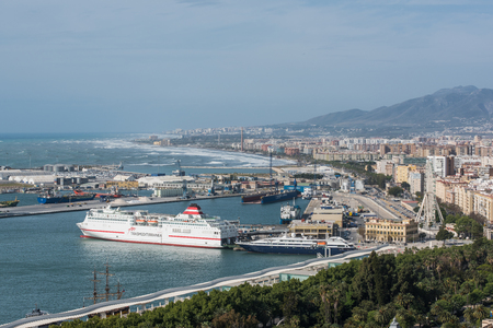 Malaga, Spain - April 20, 2017:  Port in Malaga at sunny day with residential buildings and cityscape.