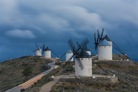 Dark thunderstorm sky and Don Quijote windmills in Consuegra. Light streak of moving car.