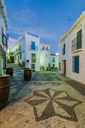 Evening illuminated narrow romantic street in Frigiliana,white viallage in Spain